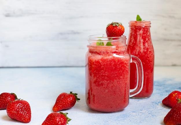 イチゴのスムージーや氷を入れたイチゴ。さわやかな夏の飲み物。白色の背景。正面図。コピースペース