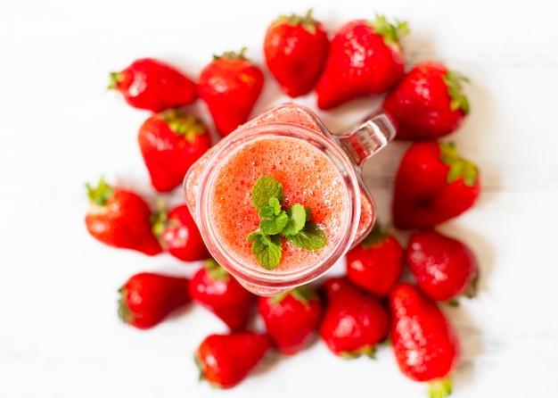 イチゴのスムージーや氷を入れたイチゴ。さわやかな夏の飲み物。白色の背景。上面図。コピースペース