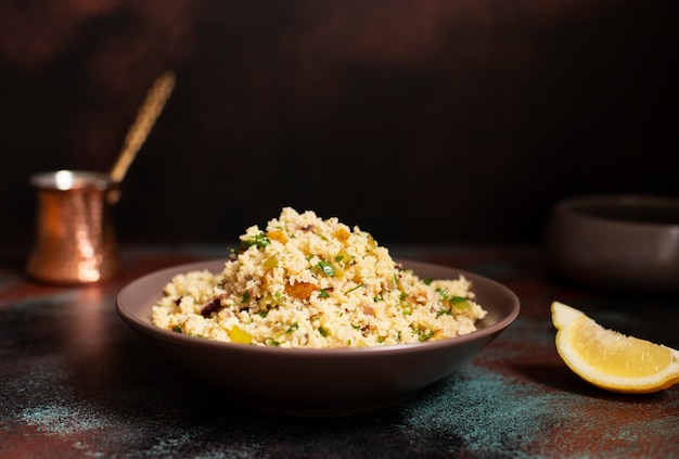 Традиционный кускус с овощами и зеленью в миску. левантинский вегетарианский салат. ливанская, арабская кухня. крупный план. копировать пространство