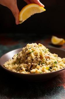Традиционный кускус с овощами и зеленью в миску. лимон в руке. левантинский вегетарианский салат. ливанская, арабская кухня. крупный план