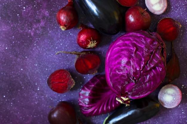 紫色の背景に紫色の果物と野菜。キャベツ、リンゴ、紫玉ねぎ、ビート、なす。同じ色の範囲の新鮮な農場の野菜と果物。上面図。コピースペース