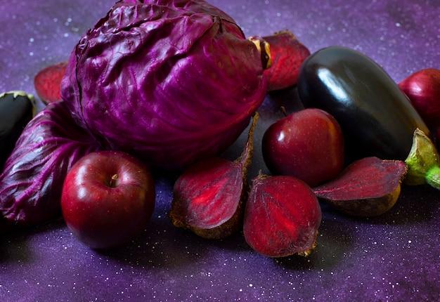 紫色の背景に紫色の果物と野菜。キャベツ、リンゴ、紫玉ねぎ、ビート、なす。同じ色の範囲の新鮮な農場の野菜と果物。閉じる。コピースペース