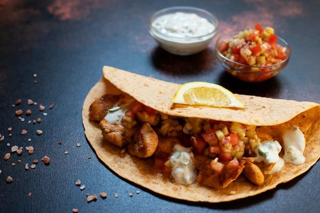 チキンと野菜の伝統的なメキシコのファヒータ。トルティーヤに白と赤のソース、レモン、新鮮なねぎを添えて。閉じる。暗い背景。コピースペース