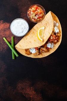 チキンと野菜の伝統的なメキシコのファヒータ。トルティーヤに白と赤のソース、レモン、新鮮なねぎを添えて。上面図。暗い背景。コピースペース