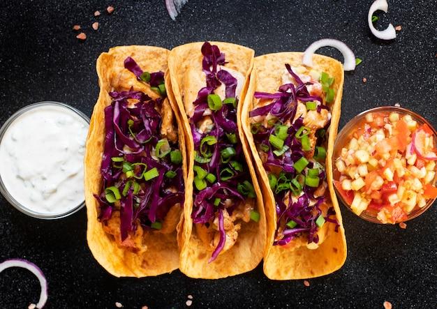 チキン、グリル野菜、玉ねぎ、紫キャベツの伝統的なメキシコのタコス。白と赤のソースが付いている。上面図。暗い背景。コピースペース