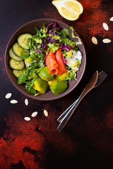 サーモン、アボカド、カボチャの種、新鮮な野菜、レモンのヘルシーダイエットサラダ。健康的な食事のコンセプトです。暗い背景、上面図、コピースペース