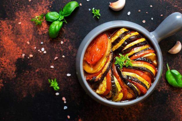 焼きたての夏野菜のラタトゥイユの伝統的なフランス料理。ベジタリアンとダイエット食品。フランス料理/食べ物。暗い素朴な背景、上面図、コピースペース