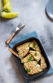 Жареный перец, фаршированный сыром и зеленью в противень. здоровое мясо без мяса. характерное блюдо балканской кухни. сербская кухня. серый фон, вид сверху, копия пространства