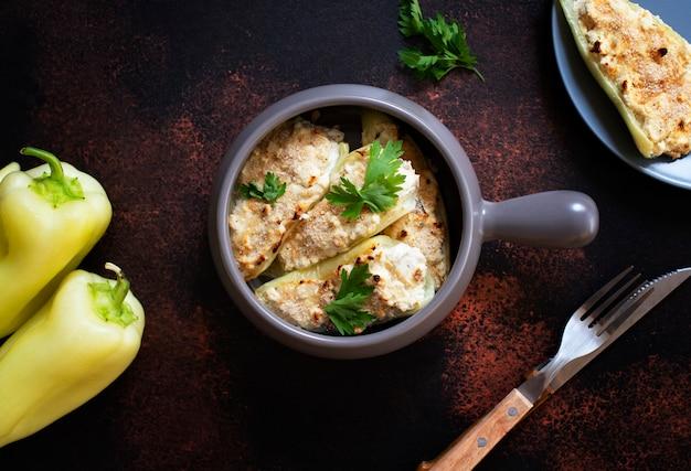 Жареный перец, фаршированный сыром и зеленью в противень. здоровое мясо без мяса. характерное блюдо балканской кухни. сербская кухня. темный деревенский фон, вид сверху, копия пространства