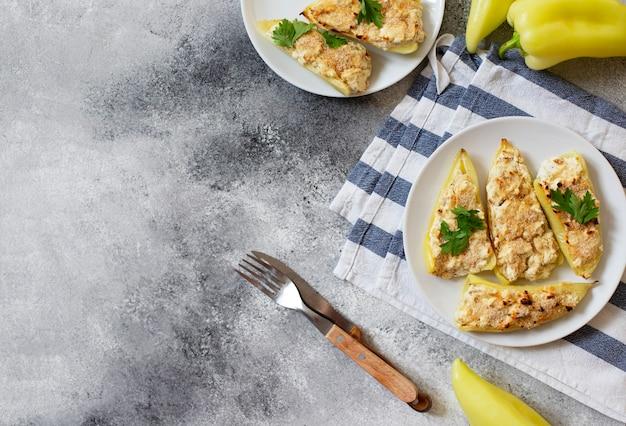Жареный перец, фаршированный сыром и зеленью на белой тарелке. характерное блюдо балканской кухни. сербская кухня. серый фон, вид сверху, копия пространства