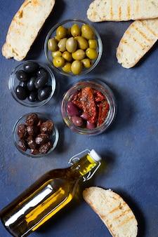 さまざまな種類のオリーブ、ブルスケッタ、天日干しトマト、オリーブオイル。地中海スナック。上面図。