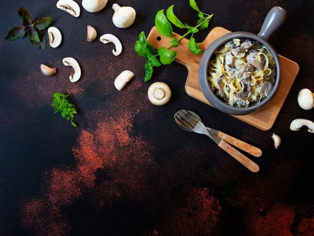 キノコとクリームソースの自家製イタリアンフェットチーネパスタとバジル(フェットチーネアルフンギポルチーニ)のグレーのフライパンで提供しています。イタリア料理。暗い素朴な背景、上面図、コピースペース