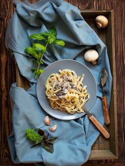 キノコとクリームソースの自家製イタリアンフェットチーネパスタとバジル(フェットチーネアルフンギポルチーニ)を添えたグレーのプレートで提供しています。伝統的なイタリア料理。暗い素朴な木製の背景、トップビュー