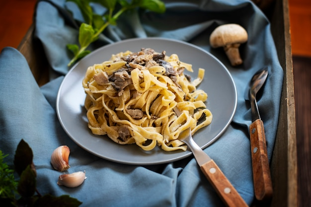 キノコとクリームソースの自家製イタリアンフェットチーネパスタとバジル(フェットチーネアルフンギポルチーニ)を添えたグレーのプレートで提供しています。伝統的なイタリア料理。暗い素朴な木製の背景、クローズアップ