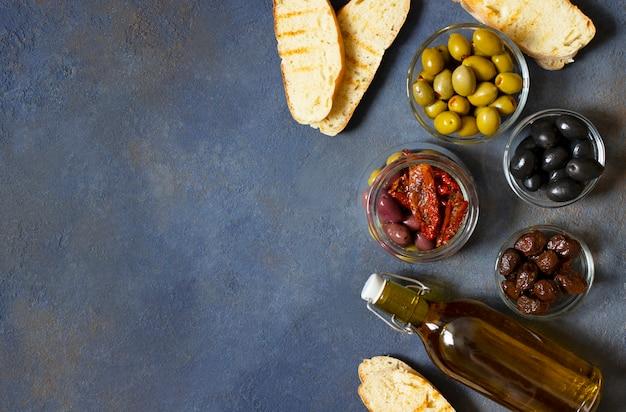 さまざまな種類のオリーブ、ブルスケッタ、天日干しトマト、オリーブオイル。地中海スナック。上面図。暗い背景。