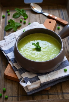 グリーンピースとブロッコリーの新鮮な自家製ダイエットクリームスープは、暗い木製のトレイにミントを添えてください。閉じる