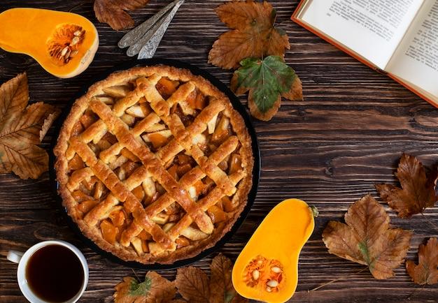 自家製パンプキンパイ。ハロウィーンと感謝祭。休日のカボチャのお菓子。木製の秋の背景、乾燥した葉、カボチャ、お茶、本をカットしました。上面図。コピースペース