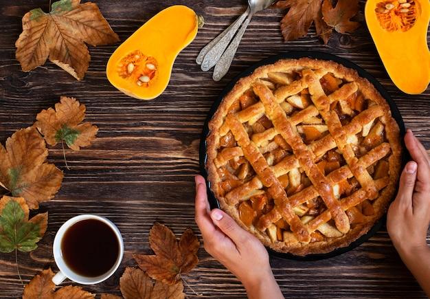 自家製のカボチャのパイを保持している女性の手。ハロウィーンと感謝祭。休日のカボチャのお菓子。木製の秋の背景、乾燥した葉、カボチャ、お茶のカップをカットしました。上面図。コピースペース