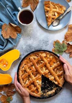 自家製カボチャのパイを保持している少女。スライスしたパンプキンパイ。一杯のお茶、紅葉、カボチャ。明るい灰色の背景、上面図、コピースペース