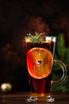グリューワインは、赤ワイン、柑橘類、果物、スパイスをクリスマスの装飾が施された木製のテーブルの上のグラスに注いだ温かい飲み物です。暗い背景。クローズアップ、カラフル、コピースペース、垂直