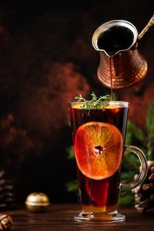 グリューワインクリスマスの装飾が施された木製のテーブルの上のグラスに赤ワイン、柑橘類、スパイスで作られた温かい飲み物。グラスに注ぐグリューワイン。暗い背景。コピースペース。閉じる