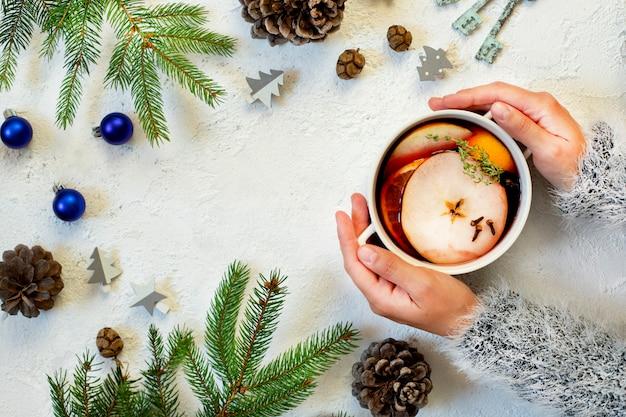 グリューワインのマグカップを保持している女性の手。赤ワイン、柑橘類、果物、スパイスから作られた温かい飲み物。冬、正月、クリスマスの飾り。平面図、フラットレイアウト。白色の背景。コピースペース