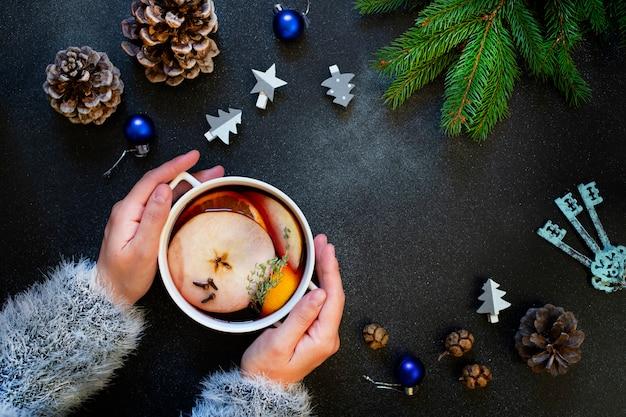グリューワインのマグカップを保持している女性の手。赤ワイン、柑橘類、果物、スパイスから作られた温かい飲み物。冬、正月、クリスマスの飾り。平面図、フラットレイアウト。暗い背景。コピースペース