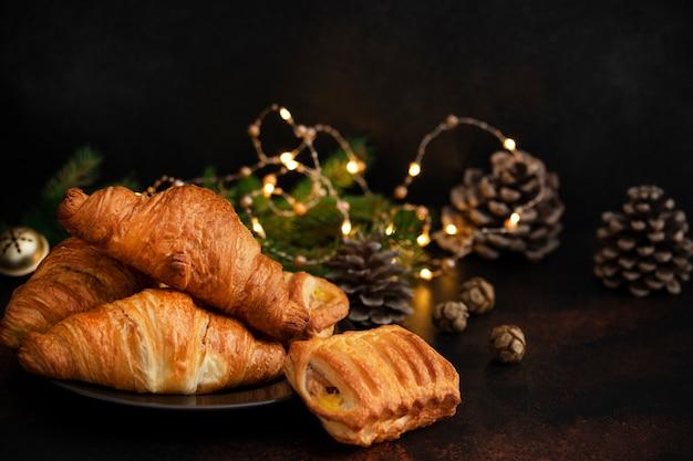Рождественская или новогодняя выпечка, шоколадные и яблочные круассаны. сочельник настроение. концепция зимних каникул. темный фон копировать пространство