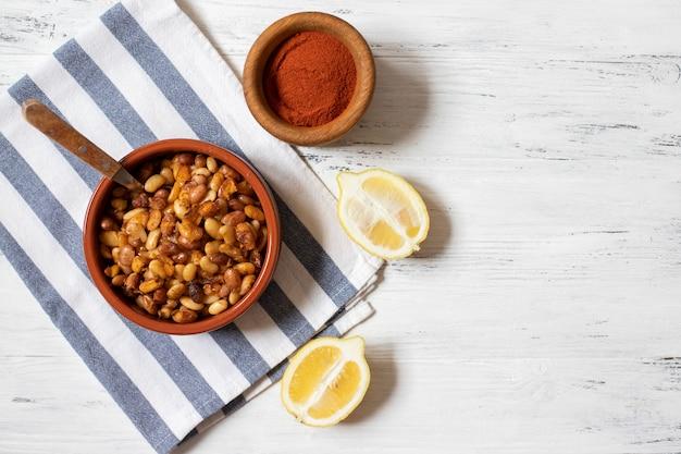 プレブラナック。バルカンのベイクドビーンズ。セルビア料理、モンテネグロ料理、ボスニア料理、クロアチア料理、スロベニア料理。生豆、玉ねぎ、レモン、パプリカパウダー。白い木製の背景。上面図。テキストのためのスペース