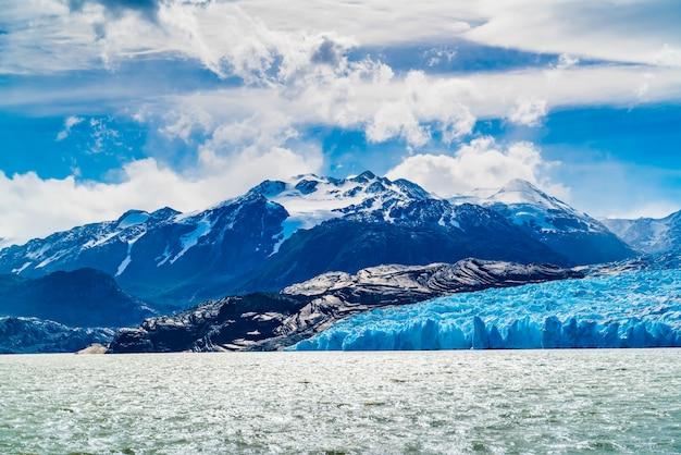 晴れた日に雪に覆われた山と灰色の氷河と灰色の湖の眺め