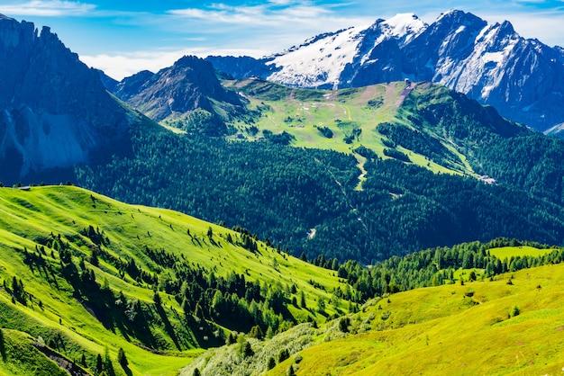 イタリアアルプス山、ドロミテ、イタリアの南チロルの雪と小さな村と緑の丘の眺め