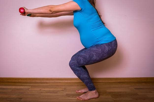 Красивая беременная в синей и серой тренировочной одежде делает выпады, когда тренируется с легкими гантелями дома.