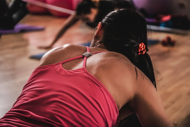 フィットネスセンターでのエクササイズ中にしゃがんだり、腕を伸ばしたりするアクティブな女性のグループ。ジムのトレーニングでスポーツの人々のグループ。