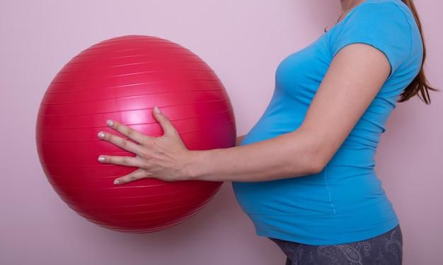 Красивая беременная женщина делает упражнения на фитнес мяч в гостиной.