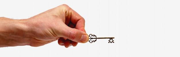 Мужская рука держа винтажный ключ изолированный на белой предпосылке. минималистичная концепция.