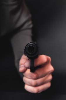 Мужская рука с пистолетом, изолированные на черном фоне. человек с пистолетом готов стрелять, сосредоточиться на оружие.