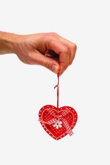 Мужская рука держа деревянное сердце изолированный на белой предпосылке. минималистичная концепция.