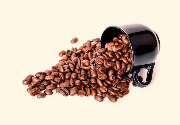 白い背景に分離された黒のセラミックカップからこぼれたコーヒー豆。コーヒーメニューに最適です。