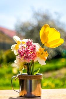 Деревенская чашка на деревянном столе с цветками, летнем саде, концепции релаксации. весенние цветы в чашке на летнем саду. сельский пейзаж в солнечном свете. летний сезон.