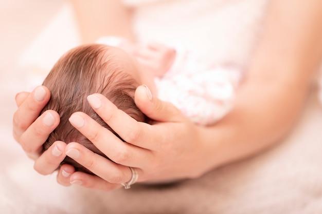 Любящая мама ухаживает за своим новорожденным ребенком дома