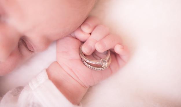 Детская рука. крупным планом руки новорожденного в руки родителей. концепция семьи с обручальные кольца в руке ребенка.