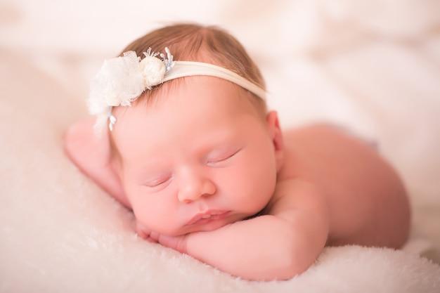 Новорожденная девочка в оголовье спит на животике