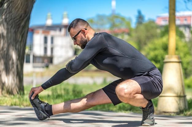 Человек растягивается на открытом воздухе в городской пейзаж, представляя модель здорового активного образа жизни.