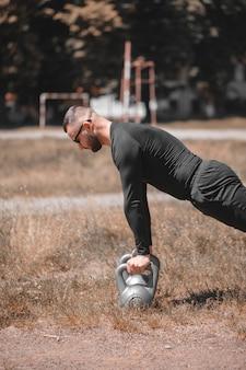 Тренировки на открытом воздухе. мужской спортсмен работая с гирей в парке.