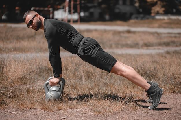 Привлекательный фитнес-инструктор делает тяжелый вес упражнения с гирей в парке. концепция фитнеса.