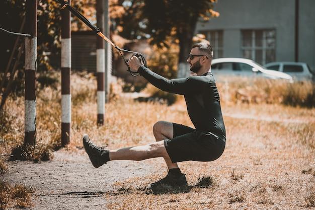 Мужчина во время тренировки с подвесными ремнями на улице