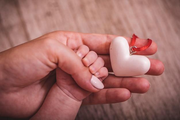 Женские руки держат руку ребенка с сердцем. всемирный день гуманитарной помощи