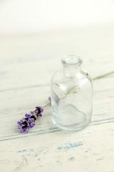 ボトルとシャビーホワイト木製テーブルの上のラベンダーの花