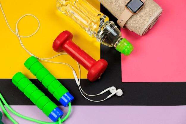 Бутылка с водой, умные часы, наушники и скакалка