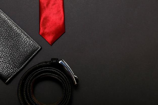 Прокат красный мужской галстук и кожаный ремень на черном фоне, вид сверху.